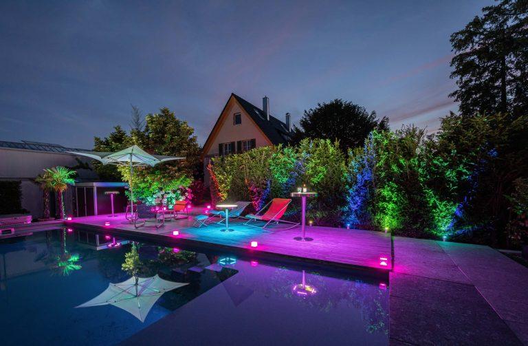 Farbenfrohe Pool Szene bei Dämmerung mit kabellosen Strahlern, Tischleuchten und Tischen