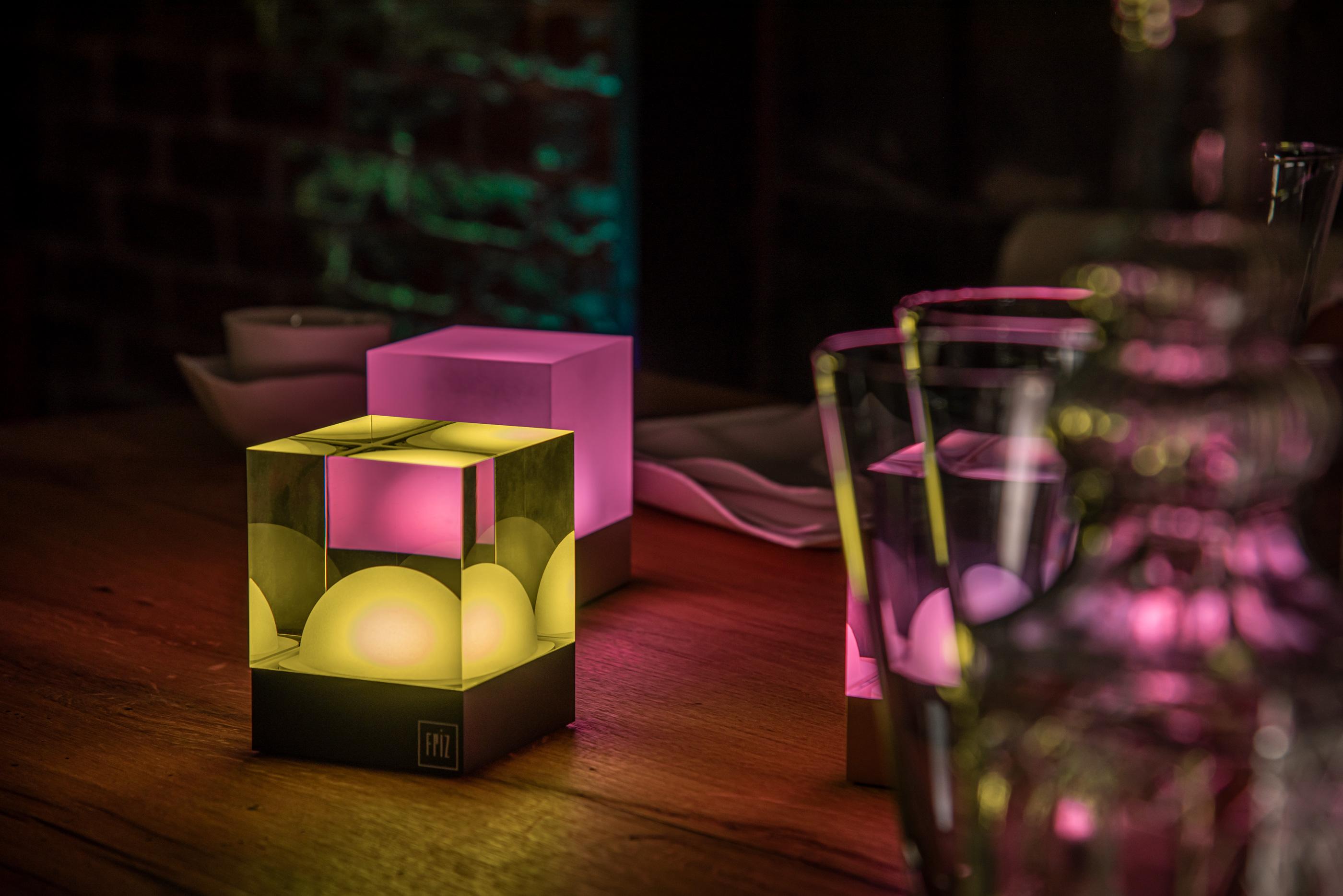 CUBEs von FRIZ bunt beleuchtet auf Holztisch